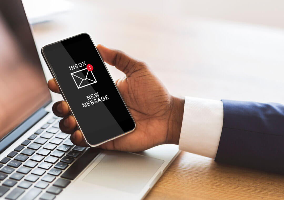 Black Businessman Holding Smartphone Reading E-Mail Message In Office